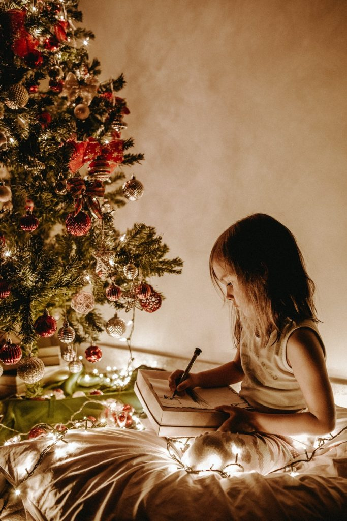 girl writing a letter to Santa for family Christmas traditions